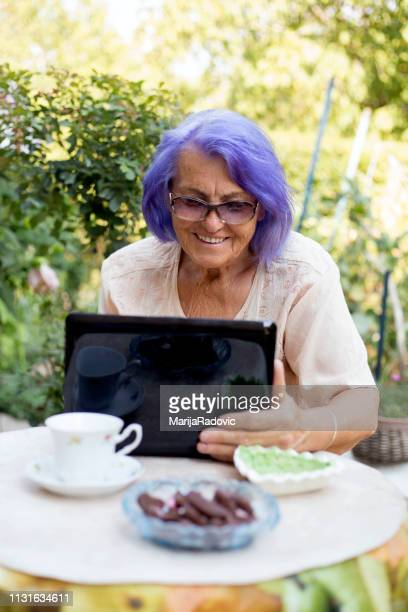 senior woman sitting in the garden at home and using a laptop - purple hair stock photos and pictures