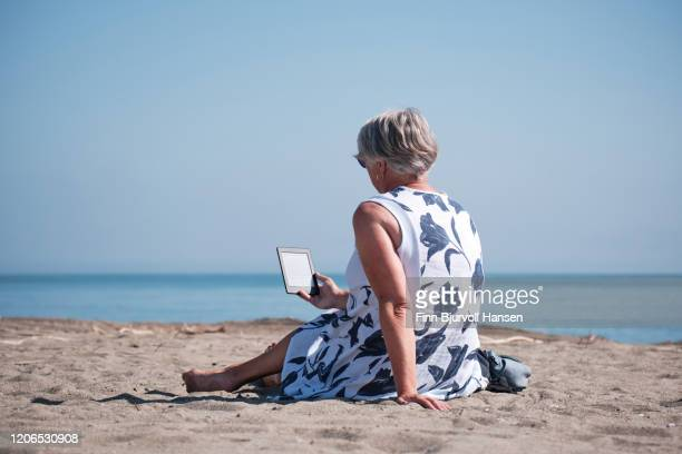 senior woman sitting in the sand at the beach reading a kindle e-book tablet - finn bjurvoll stock pictures, royalty-free photos & images