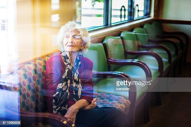 Senior woman sitting in waiting room at doctor office