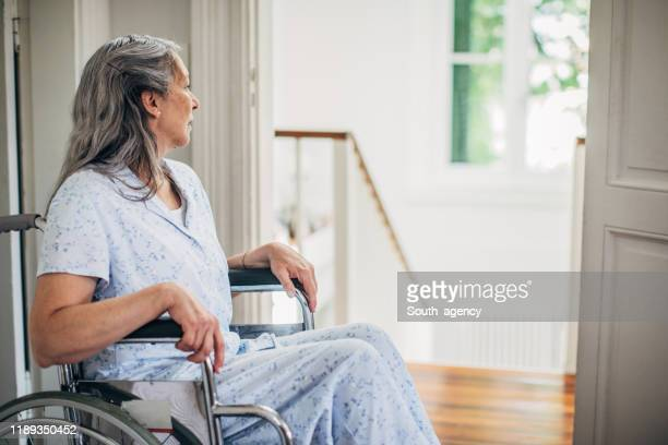 senior woman sitting in wheelchair at home - persons with disabilities stock pictures, royalty-free photos & images