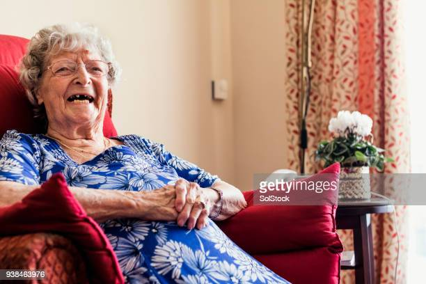 senior woman sitting laughing - fragility stock pictures, royalty-free photos & images