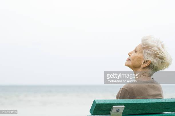 Senior woman sitting near sea, looking at view