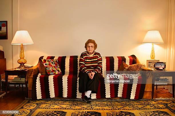 senior woman sitting on a sofa - soledad fotografías e imágenes de stock