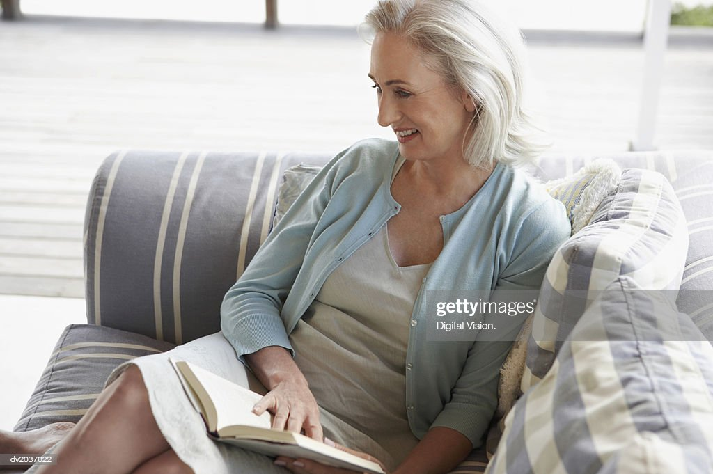 Senior Woman Sitting on a Sofa With a Book : Stock Photo