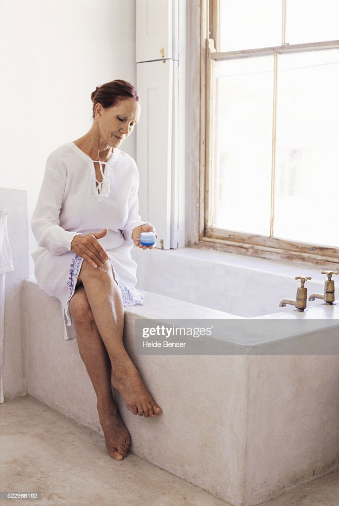 Senior Woman Sitting On Bathtub Applying Lotion To Her Leg : Stock Photo