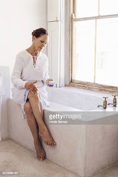 Senior woman sitting on bathtub applying lotion to her leg