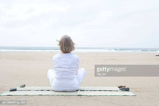 senior woman sitting on beach, looking at sea, rear view - one senior woman only stock pictures, royalty-free photos & images