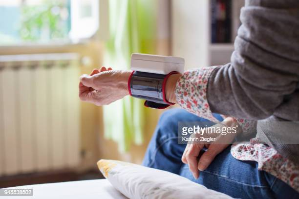 senior woman sitting on bed, measuring her blood pressure - blood pressure gauge stock pictures, royalty-free photos & images
