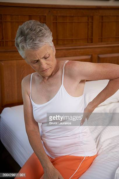 Senior woman sitting on bed with hand on back