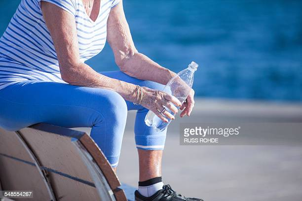 senior woman sitting on bench by sea holding bottled water - old women in pantyhose stock photos and pictures