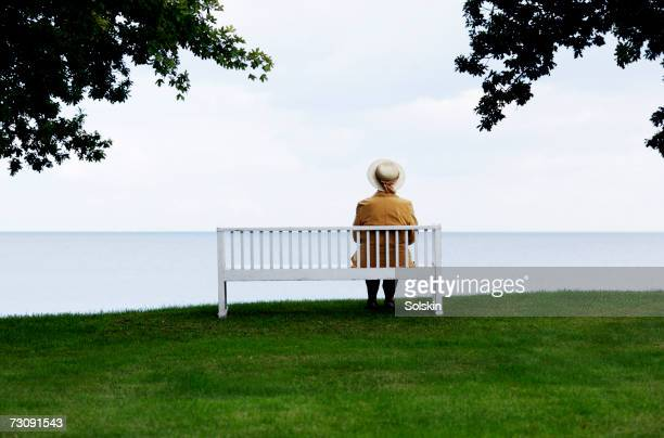 senior woman sitting on bench looking out to sea, rear view - one senior woman only stock pictures, royalty-free photos & images
