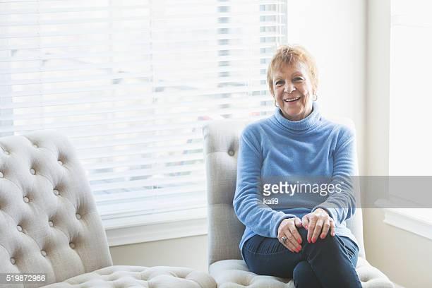 Senior woman sitting on chair by window