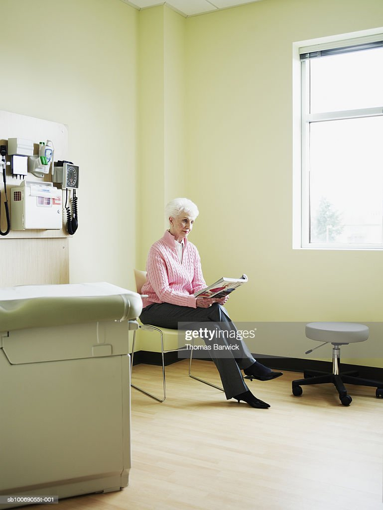 Senior woman sitting on chair in exam room reading magazine : Stockfoto