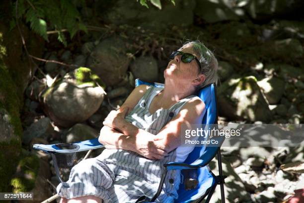 senior woman sitting on chair in the forest