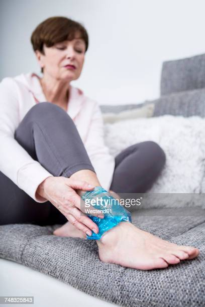 senior woman sitting on couch, cooling sprained ankle - sprain stock pictures, royalty-free photos & images