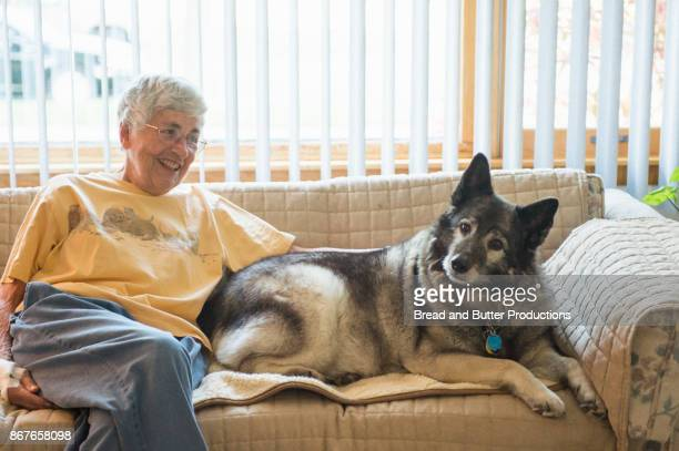 Senior Woman Sitting on Couch in Livingroom with her Norwegian Elkhound Dog