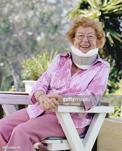 Senior woman sitting on deck chair, wearing neck brace, portrait
