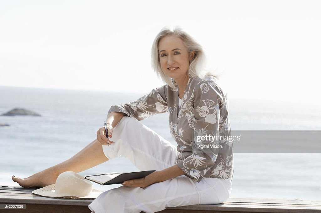 Senior Woman Sitting on Decking by the Coast With a Pen and Her Diary : Stock Photo