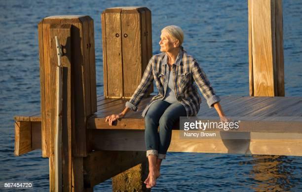 senior woman sitting on dock by water in thoughtful mood. - só uma mulher idosa imagens e fotografias de stock