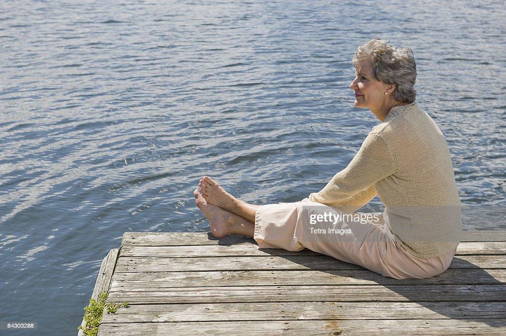 Senior woman sitting on dock : Stock-Foto