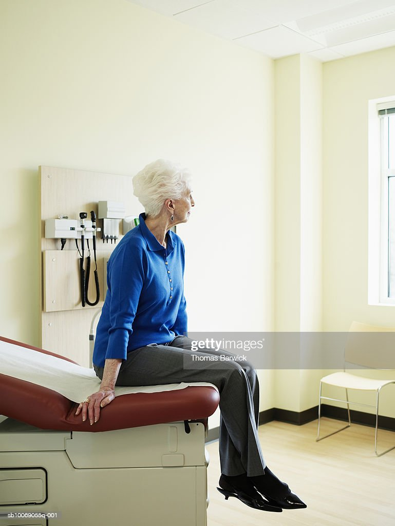 Senior woman sitting on examination table, looking away : Stockfoto