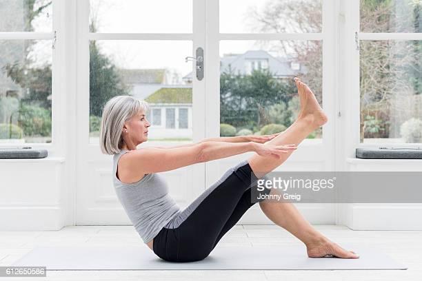 Senior woman sitting on floor stretching leg