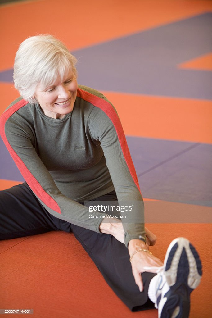 Senior woman sitting on floor, stretching : Stock Photo