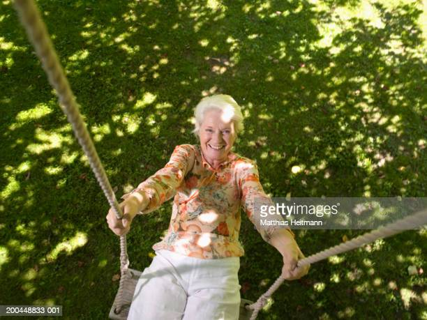 Senior woman sitting on garden swing, smiling, portrait, overhead view