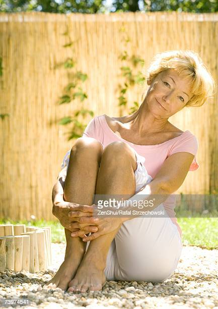 senior woman sitting on ground outdoors - older woman legs stock photos and pictures