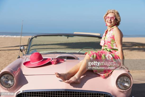 Senior woman sitting on hood of convertible at the beach