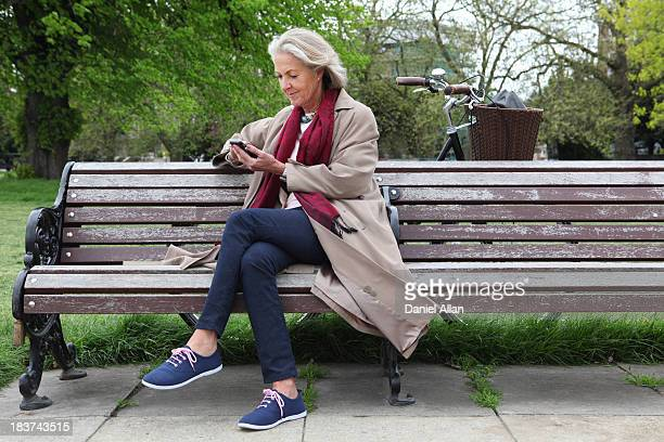 senior woman sitting on park bench and looking at mobile phone - park bench stock pictures, royalty-free photos & images