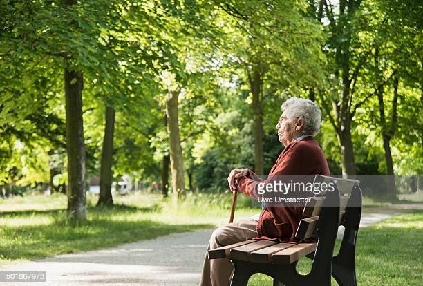 Senior woman sitting on park bench