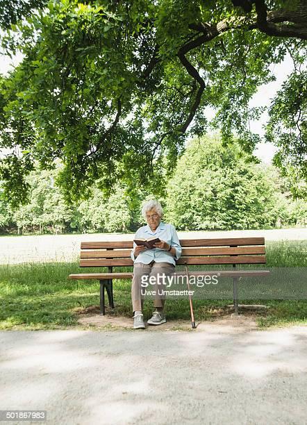Senior woman sitting on park bench reading bible