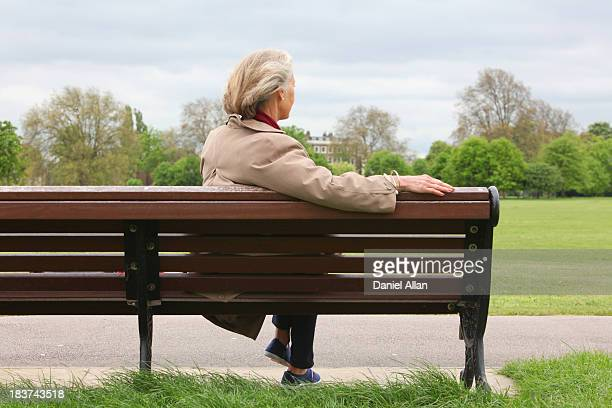 Senior woman sitting on park bench, rear view