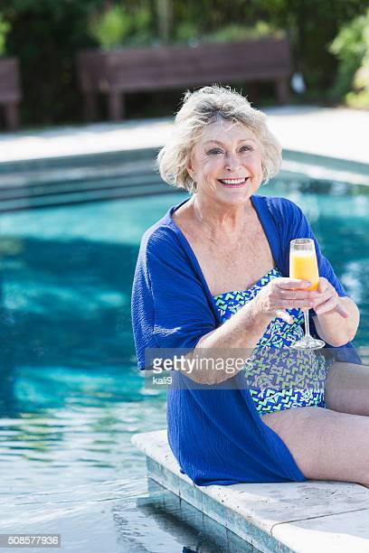 senior woman sitting on pool deck with drink - old woman in swimsuit stock pictures, royalty-free photos & images
