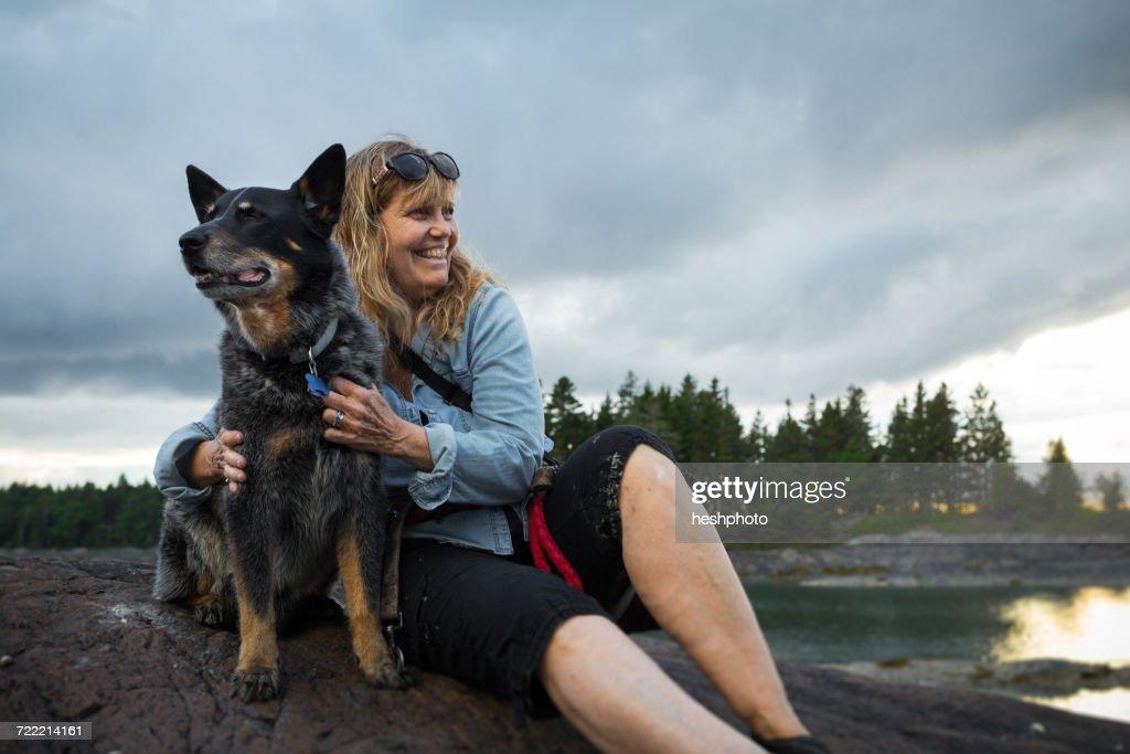 Senior woman sitting on rock hugging dog at coast of Maine, USA : Stock Photo