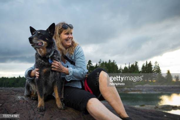 senior woman sitting on rock hugging dog at coast of maine, usa - heshphoto stock pictures, royalty-free photos & images