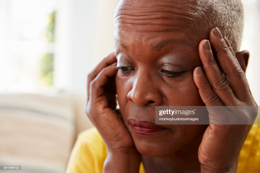 Senior Woman Sitting On Sofa At Home Suffering From Depression : Stock Photo