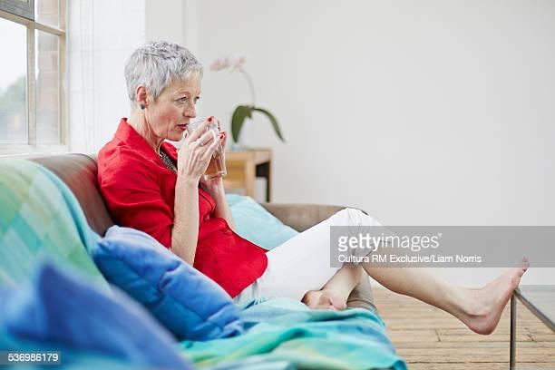 Senior woman sitting on sofa drinking herbal tea