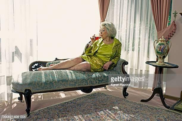 Senior woman sitting on sofa, drinking wine, side view