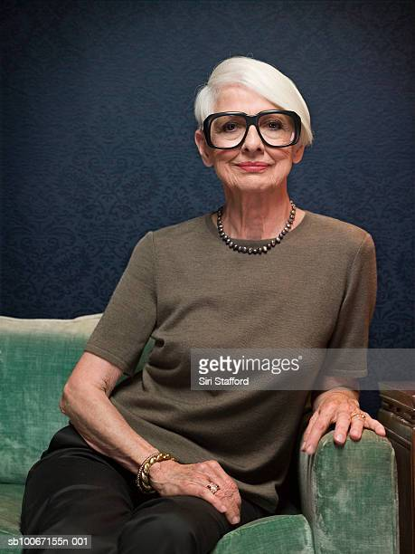 senior woman sitting on sofa wearing oversized glasses, portrait - big bobs stock photos and pictures