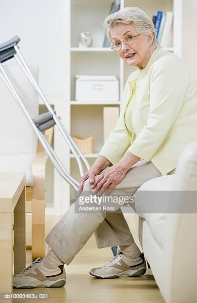 Senior woman sitting on sofa with crutches, holding knee, portrait