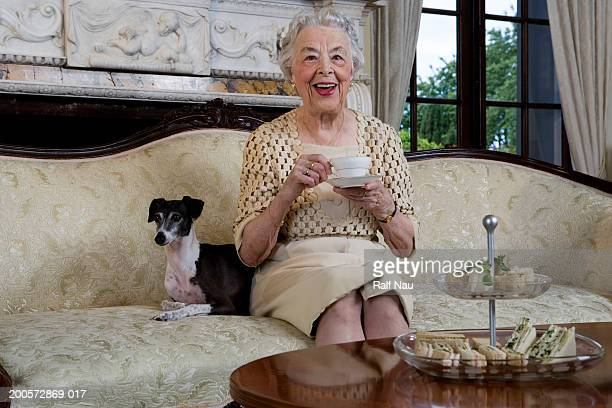 Senior woman sitting on sofa with dog, smiling