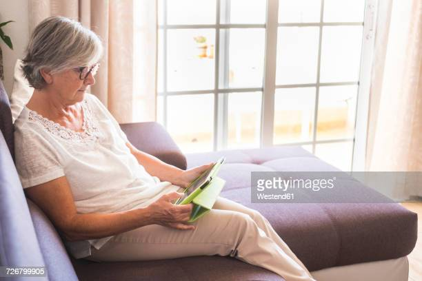 Senior woman sitting on the couch using tablet