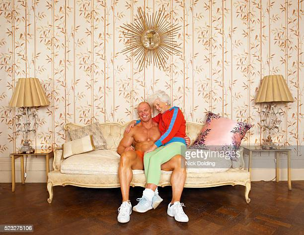 senior woman sitting on the lap of a young muscular man - gegensatz stock-fotos und bilder