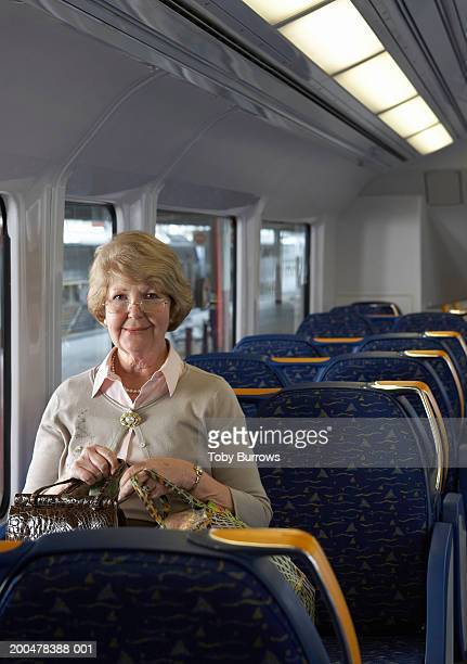 Senior woman sitting on train holding bags, smiling, portrait