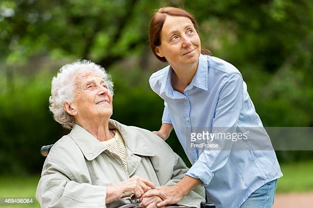Senior woman sitting on wheelchair with home caregiver