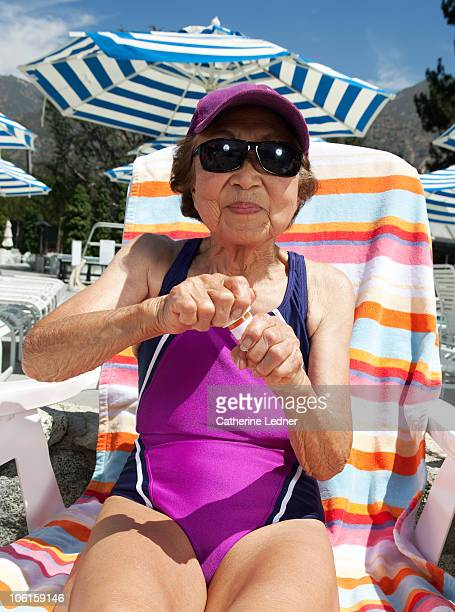 Senior woman sitting out by pool
