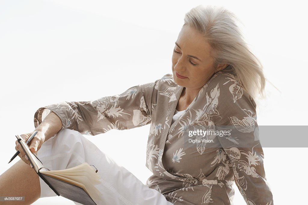 Senior Woman Sitting Outdoors and Reading Her Diary : Stock Photo
