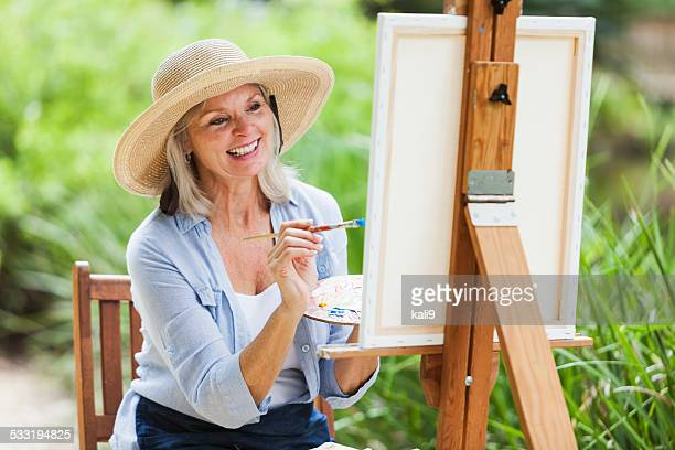 Senior Frau sitzt im Freien, Gemälde